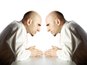 Double portrait of a businessman facing himself