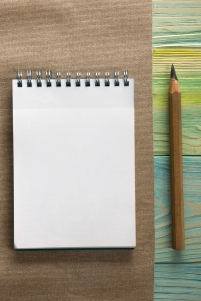 Back to school. Blank notepad book, pen on wooden background
